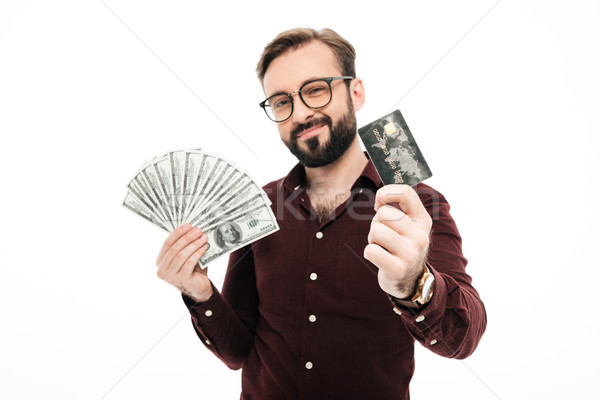 Happy thinking young man holding money and credit card. Stock photo © deandrobot