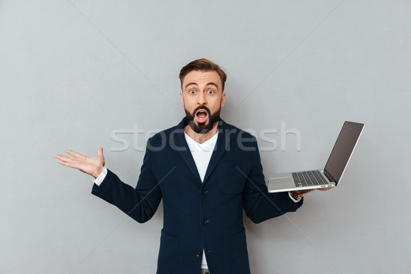 Shocked man holding laptop computer and looking camera with opened mouth isolated Stock photo © deandrobot