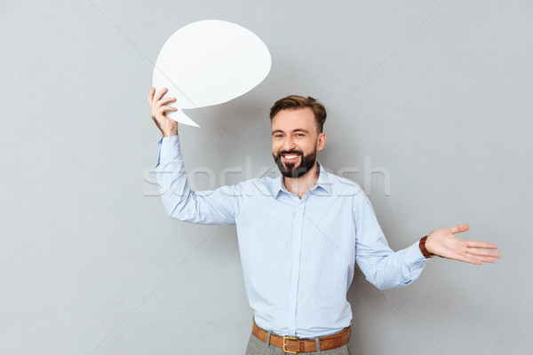 Smiling bearded man in business clothes holding blank speech bubble Stock photo © deandrobot