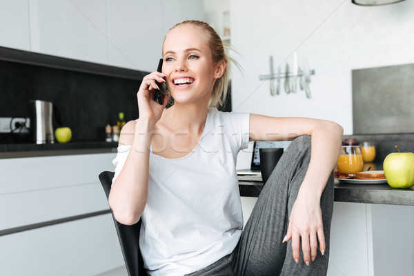 Happy beautiful lady looking aside while talking on phone Stock photo © deandrobot