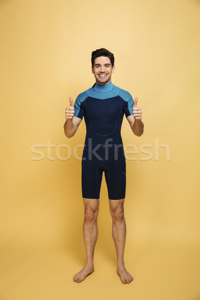 Joyful young man dressed in swimsuit Stock photo © deandrobot