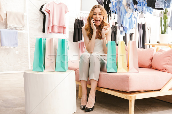 Cheerful young woman sitting at the clothing store Stock photo © deandrobot