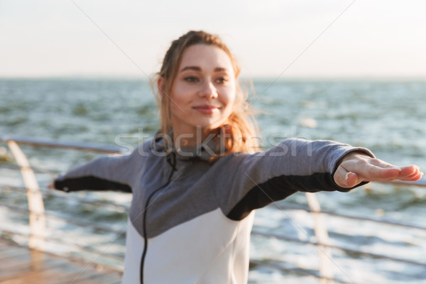 Smiling young girl standing in yoga pose Stock photo © deandrobot