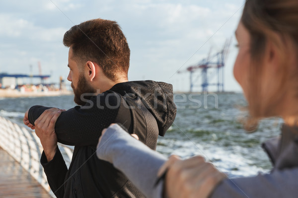 Motivated young sports couple doing stretching Stock photo © deandrobot