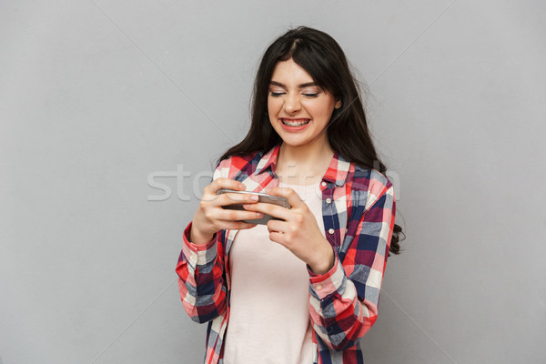 Cute young lady play games by mobile phone. Stock photo © deandrobot