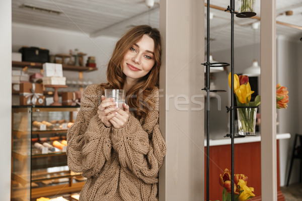 Photo of relaxed woman 20s looking on camera, and drinking glass Stock photo © deandrobot