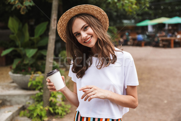 Happy young girl holding take away coffee cup Stock photo © deandrobot