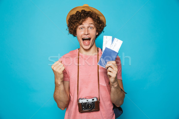 Image of happy traveler man 18-20 with curly hair wearing backpa Stock photo © deandrobot