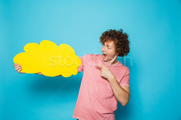 Photo of handsome cheerful man 20s with brown curly hair holding Stock photo © deandrobot