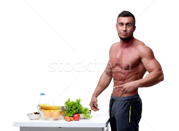 Handsome muscular man pointing at healthy food Stock photo © deandrobot