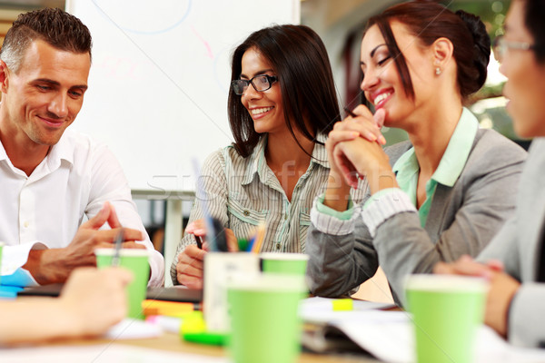 Szczęśliwy ludzi biznesu posiedzenia około tabeli spotkanie Zdjęcia stock © deandrobot