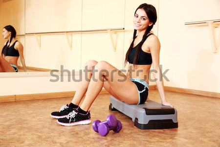 Young smiling fit woman sitting on yoga mat and looking away at gym Stock photo © deandrobot