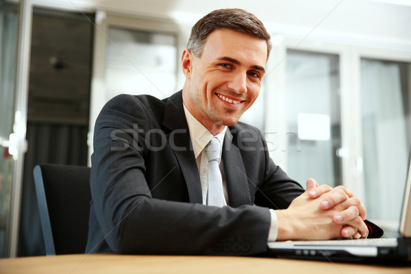 Happy businessman sitting with laptop at office Stock photo © deandrobot