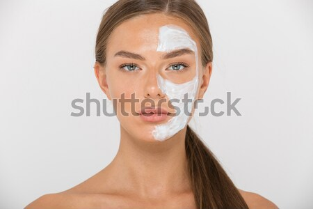 Portrait of a beautiful woman cleaning her face with cosmetic wad Stock photo © deandrobot