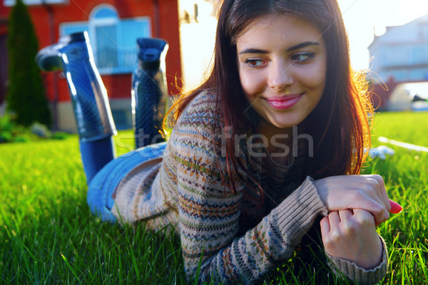 Thoughtful woman lies on the lawn and looking away Stock photo © deandrobot