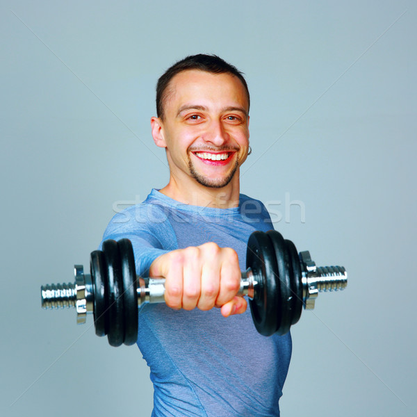 Happy man working out with dumbbells over gray background Stock photo © deandrobot