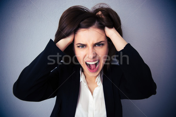 Angry businesswoman shouting over gray background Stock photo © deandrobot