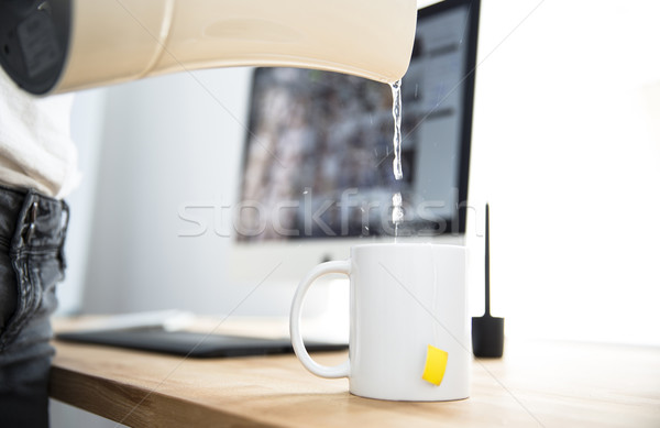 Woman with kettle pouring water in a cup Stock photo © deandrobot