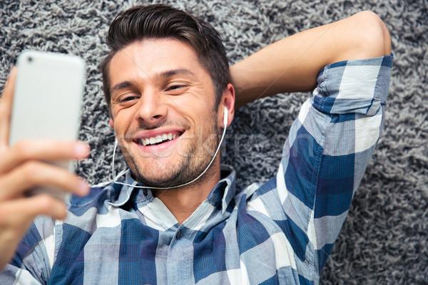 Man using smarpthone on the floor Stock photo © deandrobot
