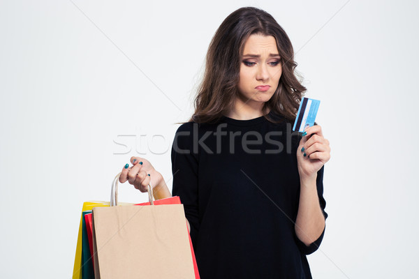 Sad woman holding shopping bags and bank Stock photo © deandrobot