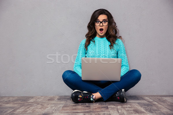 Shocked woman sitting on the floor with laptop  Stock photo © deandrobot