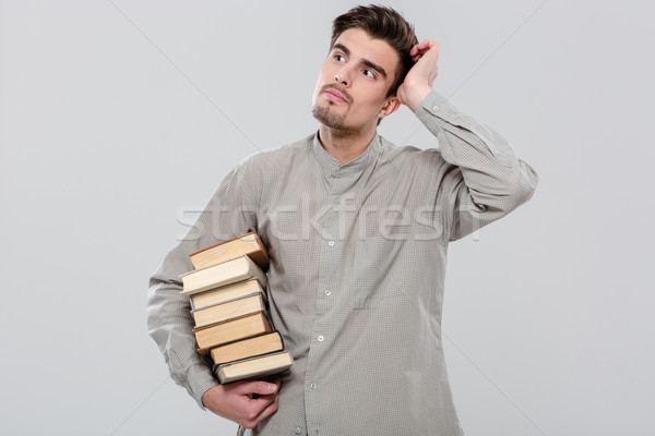 Young handsome man thinking and holding books Stock photo © deandrobot