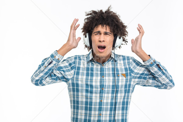 Shocked afro american man in headphoes listening music Stock photo © deandrobot