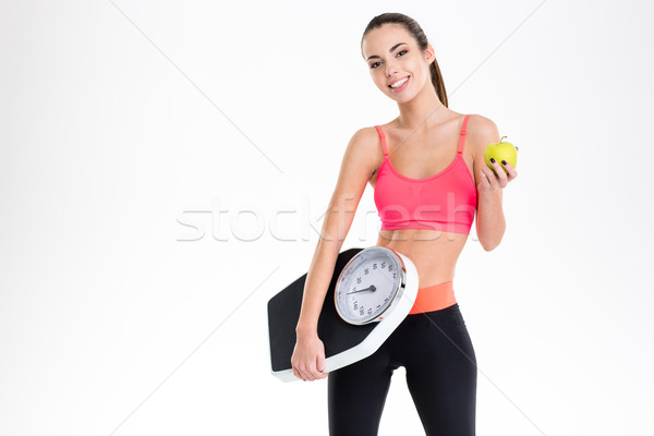 Cheerful beautiful fitness woman holding weighing scale and yellow apple Stock photo © deandrobot
