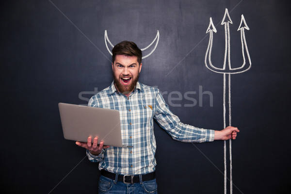 Angry man using laptop and holding trident drawn on blackboard  Stock photo © deandrobot
