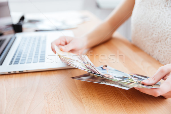 Photos holded by young woman photographer in the office Stock photo © deandrobot