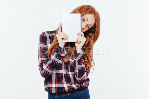 Woman peeping from tablet computer Stock photo © deandrobot