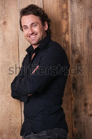 Cheerful handsome man in black shirt standing with arms crossed  Stock photo © deandrobot