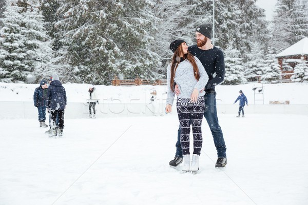 Couple in ice skates hugging and looking at each other Stock photo © deandrobot