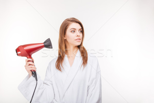 Beautiful thoughful woman in bathrobe drying her hair with dryer  Stock photo © deandrobot