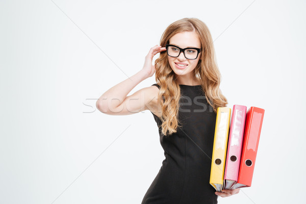 Charming smiling young businesswoman in glasses holding colorful folders  Stock photo © deandrobot