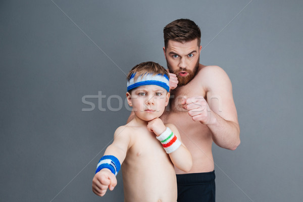 Serious bearded father and his little son punching at camera Stock photo © deandrobot