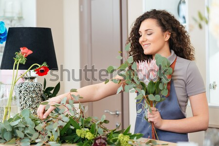 Smiling woman florist standing and making bouquet in flower shop Stock photo © deandrobot