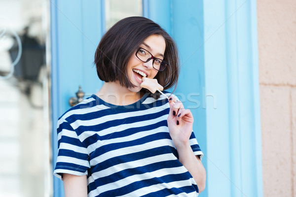 Cheerful woman in glasses eating star shaped lollipop  Stock photo © deandrobot