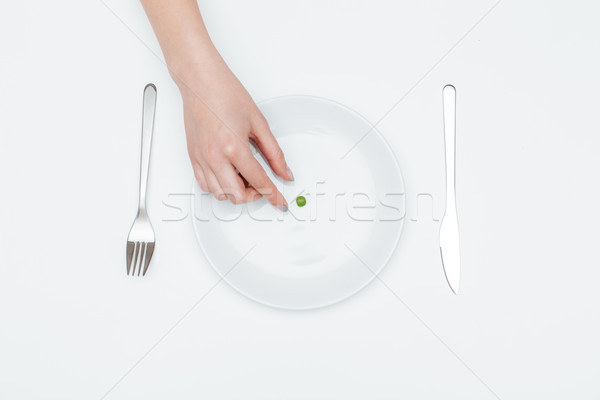 Woman hand taking one green pea from the plate Stock photo © deandrobot