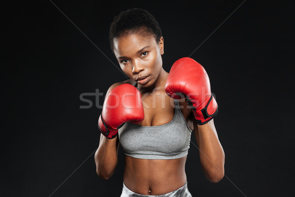 Fitness girl in boxing gloves fighting on black background Stock photo © deandrobot