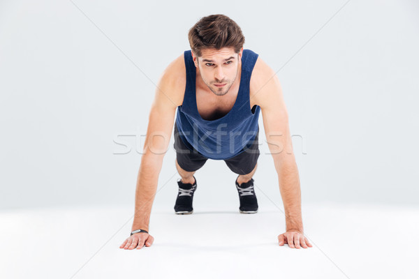 Handsome young man athlete training and doing plank exercise Stock photo © deandrobot