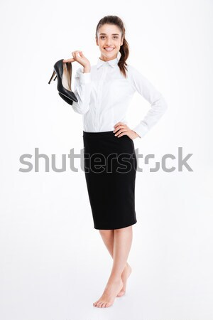 Smiling young businesswoman standing barefoot and holding high heels shoes Stock photo © deandrobot