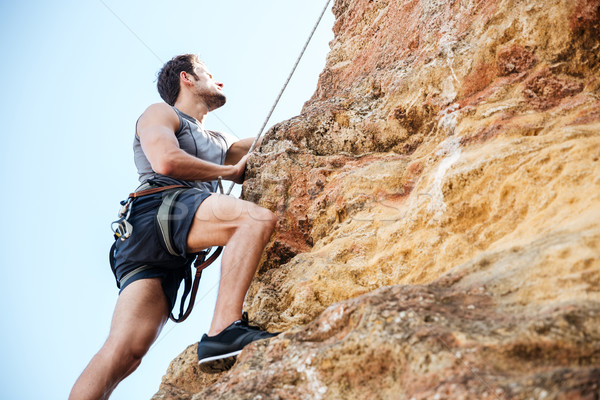 Young man climbing natural rocky wall Stock photo © deandrobot