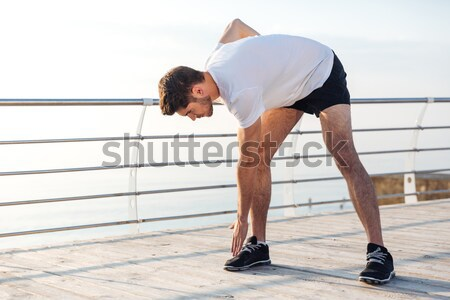 Male athlete stretching and warming up before jogging in morning Stock photo © deandrobot