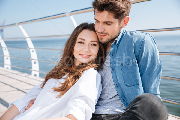 Portrait of a young happy couple sitting outdoors Stock photo © deandrobot