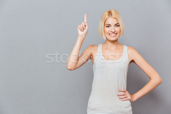 Smiling cute young woman pointing up Stock photo © deandrobot