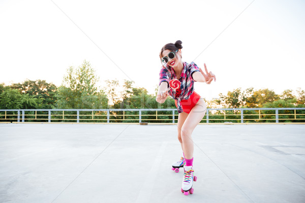 Woman with lollipop on roller skates showing peace sign Stock photo © deandrobot
