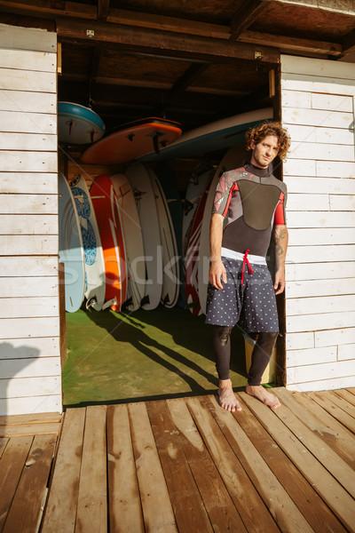 Fürtös férfi fürdőruha áll tengerparti kunyhó fiatal Stock fotó © deandrobot