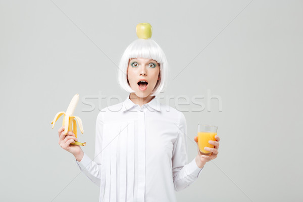 Wondered young woman with apple on her head holding banana Stock photo © deandrobot