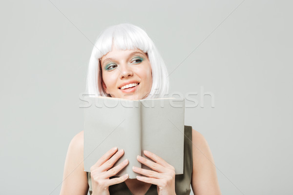 Happy woman in blonde wig smiling and reading a book Stock photo © deandrobot